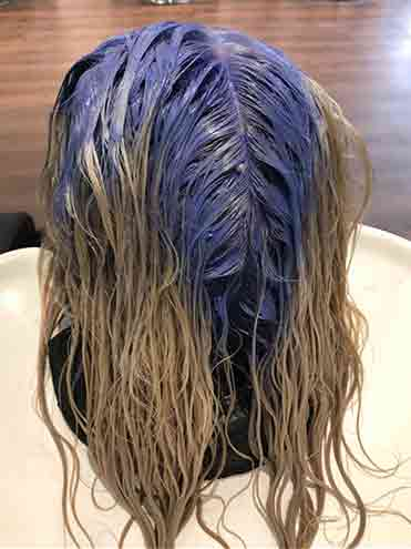 Woman in salon with purple bleach on roots