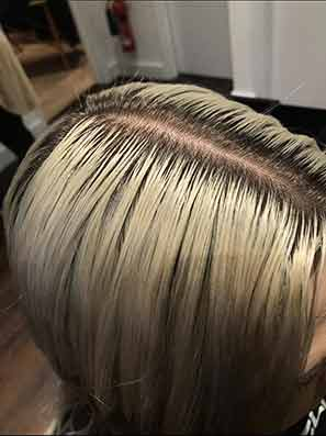 Close up of a woman's blonde roots hair