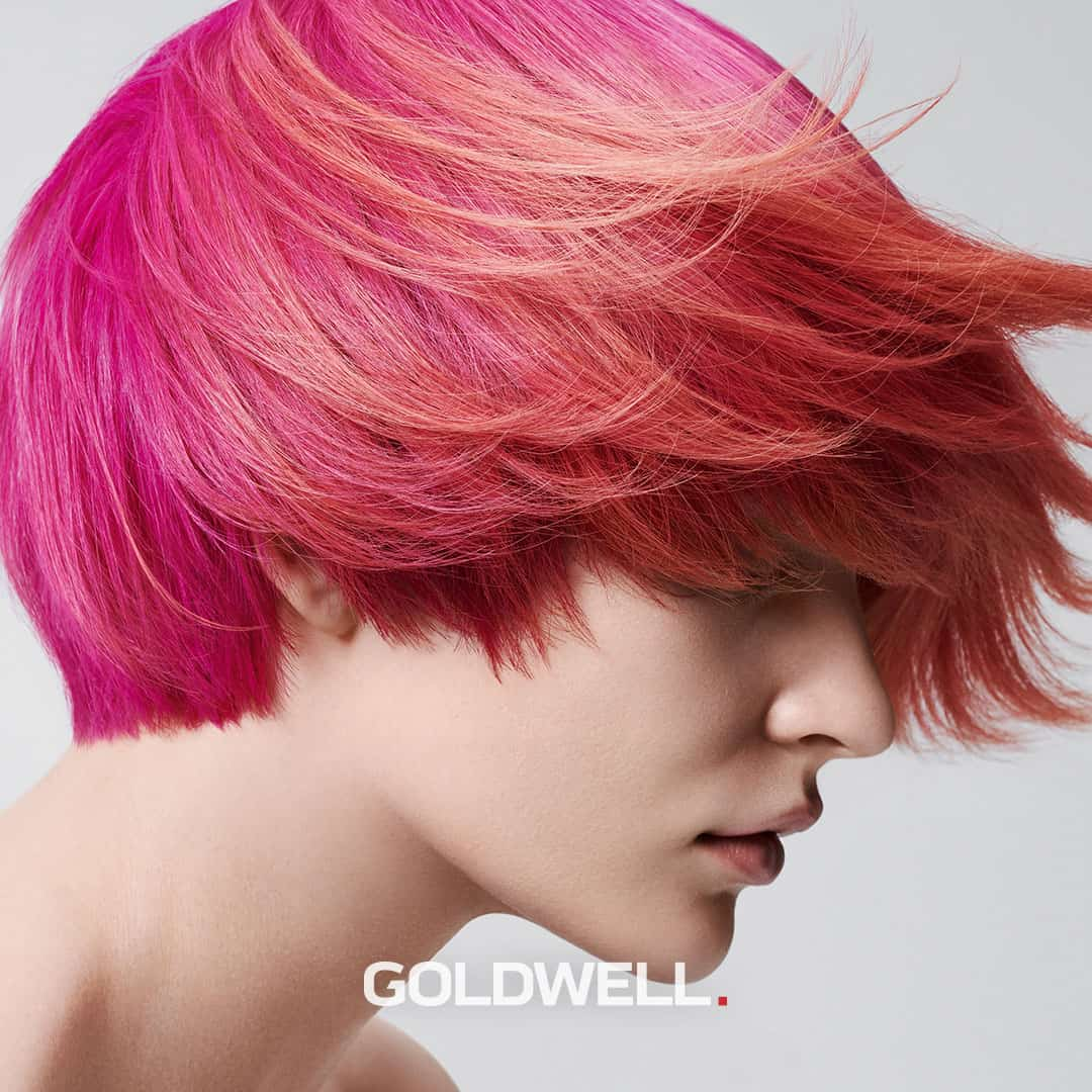 Woman with bright pink short hair over her face.